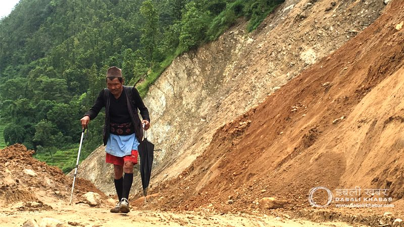 old man walking in flood area nuwakot